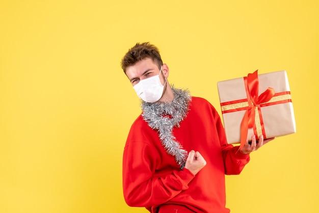 Jovem do sexo masculino segurando um presente de natal com máscara estéril