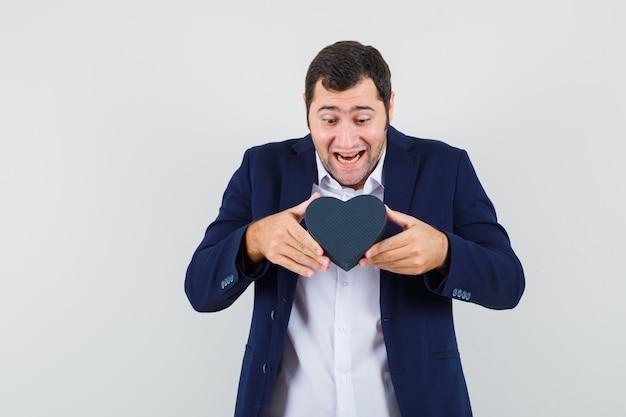Jovem do sexo masculino segurando uma caixa de presente na camisa