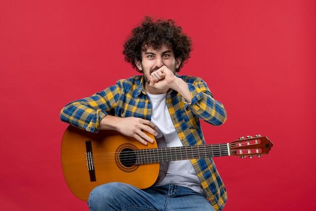 Jovem do sexo masculino sentado com a guitarra na parede vermelha tocar de frente para tocar música ao vivo cor músico aplausos banda