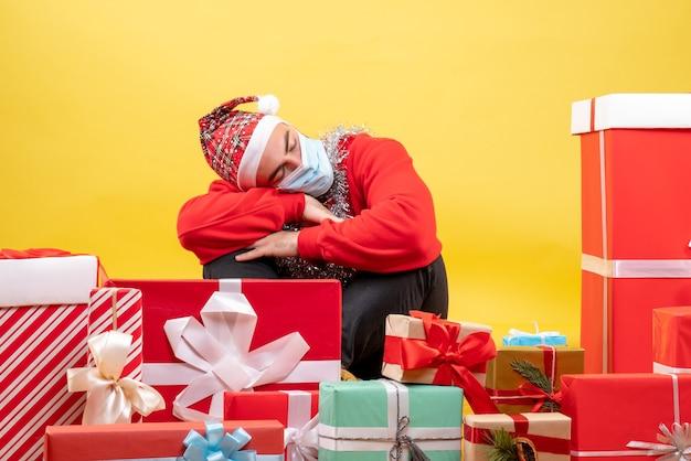 Jovem do sexo masculino sentado de frente para um presente dormindo sobre fundo amarelo