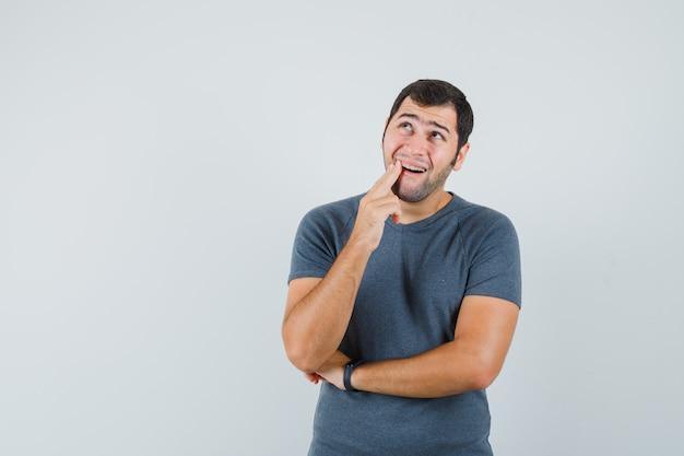 Jovem do sexo masculino sofrendo de dor de dente, vestindo uma camiseta cinza e parecendo desconfortável
