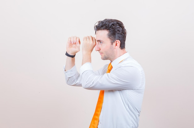 Jovem, dobrando as mãos em forma de telescópio na camisa branca e curioso.