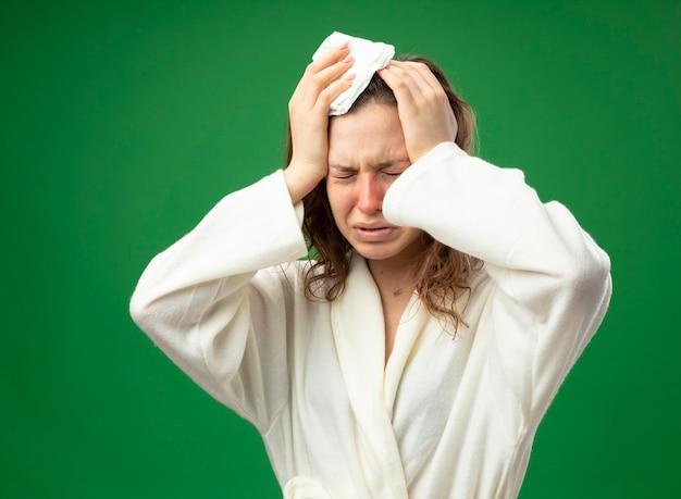 Jovem doente a chorar com os olhos fechados e uma túnica branca agarrada à cabeça