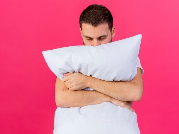 Jovem doente abraçou travesseiro isolado em rosa Foto gratuita