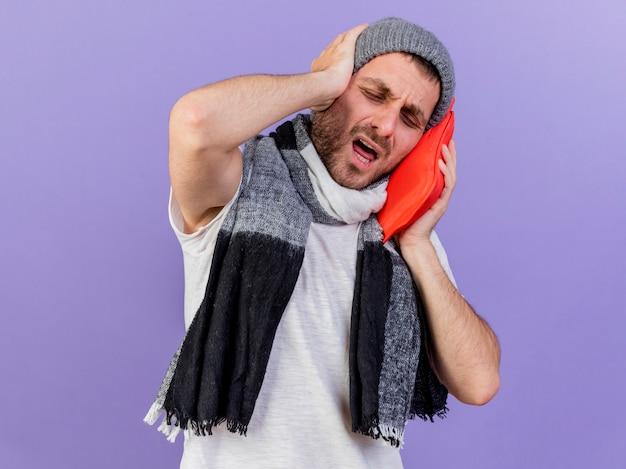 Jovem doente arrependido usando chapéu de inverno com lenço segurando uma garrafa de água quente na bochecha e agarrando a cabeça isolada no roxo