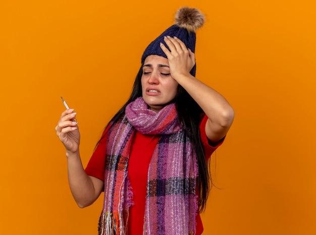Jovem doente caucasiana dolorida com chapéu de inverno e lenço segurando e olhando para o termômetro isolado na parede laranja com espaço de cópia