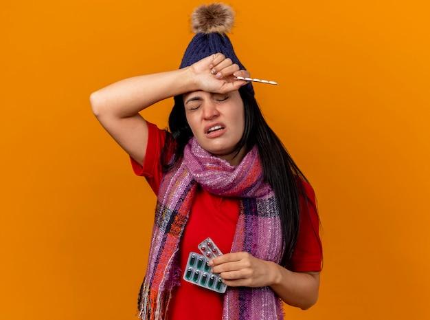 Jovem doente caucasiana dolorida com chapéu de inverno e lenço segurando pacotes de cápsulas e comprimidos, colocando a mão na cabeça com os olhos fechados, isolados na parede laranja com espaço de cópia