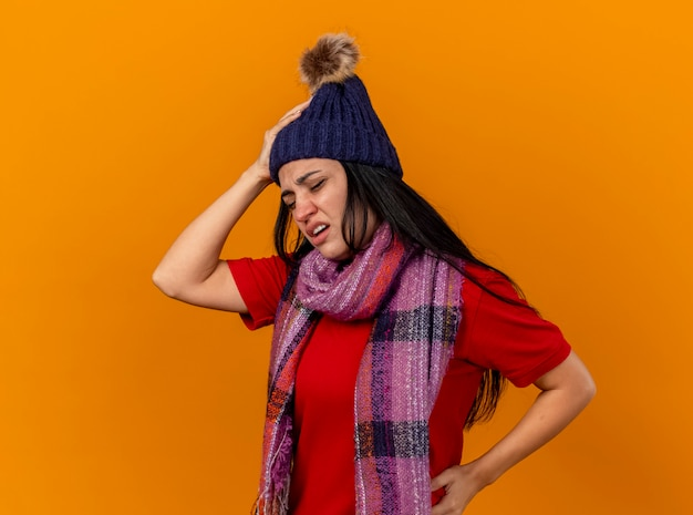 Jovem doente caucasiana dolorida com chapéu e lenço de inverno, mantendo as mãos na cabeça e na cintura, com os olhos fechados, isolados na parede laranja com espaço de cópia