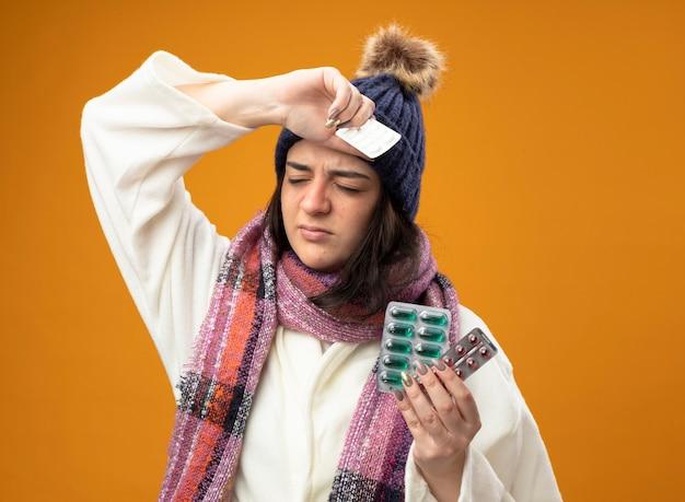 Jovem doente caucasiana dolorida usando um manto de inverno, chapéu e cachecol, segurando pacotes de cápsulas e comprimidos mantendo as mãos na cabeça com os olhos fechados, isolados na parede laranja