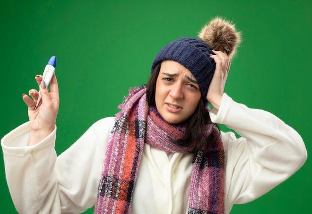 Jovem doente caucasiana dolorida usando um manto de inverno, chapéu e lenço segurando um termômetro e mantendo a mão na cabeça isolada na parede verde