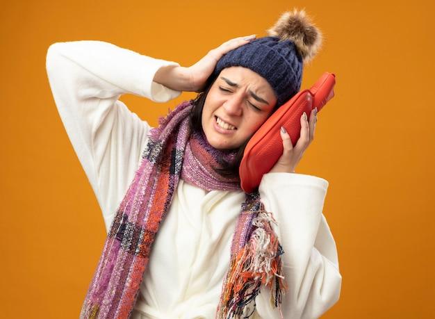Jovem doente caucasiana dolorida usando um manto de inverno, chapéu e lenço tocando a cabeça com uma bolsa de água quente, mantendo a mão na cabeça com os olhos fechados, isolada na parede laranja com espaço de cópia
