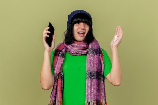 Jovem doente caucasiana impressionada com chapéu de inverno e lenço segurando o celular e o guardanapo, olhando para o lado, levantando a mão isolada no fundo verde oliva com espaço de cópia