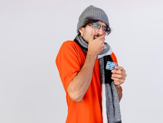 Jovem doente, caucasiano, dolorido, usando óculos, chapéu e cachecol, segurando um pacote de cápsulas médicas, mantendo a mão na boca, tendo uma dor de dente isolada no fundo branco com espaço de cópia