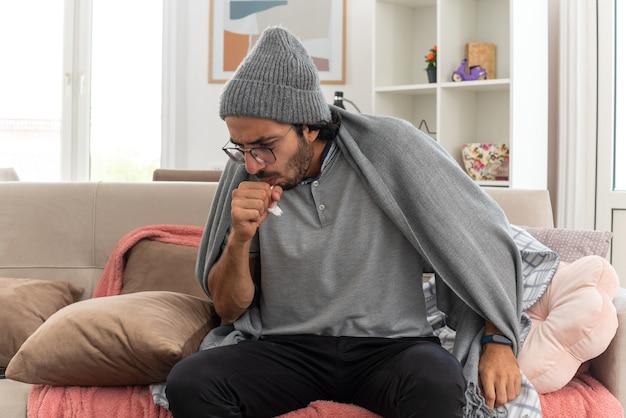 Jovem doente, caucasiano, usando óculos óticos, usando um chapéu de inverno, tossindo e mantendo o punho fechado perto da boca, sentado no sofá da sala