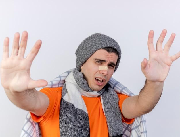 Jovem doente com chapéu de inverno e cachecol embrulhado em xadrez com gesso no nariz estendendo as mãos para a câmera