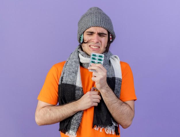Jovem doente com chapéu de inverno e lenço colocando comprimidos sob o chapéu e segurando comprimidos isolados no roxo