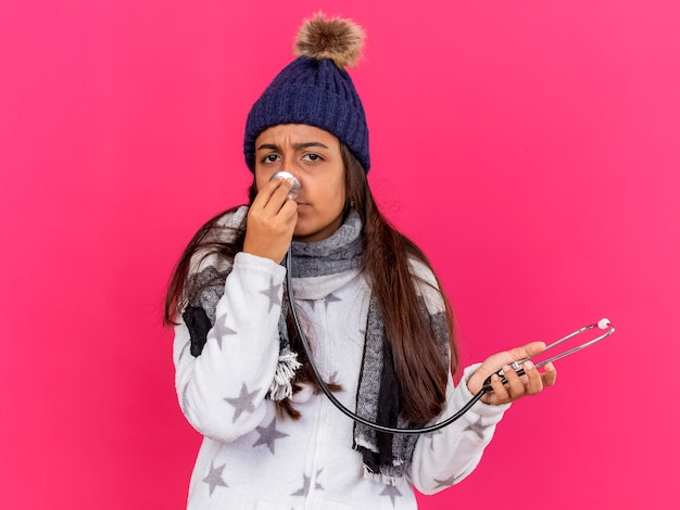 Jovem doente com chapéu de inverno e lenço segurando e colocando o estetoscópio no nariz isolado na rosa