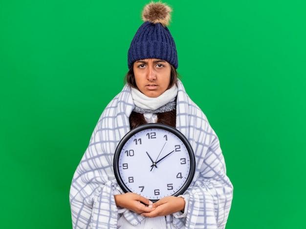 Jovem doente com chapéu de inverno e lenço segurando um relógio de parede isolado no fundo verde.