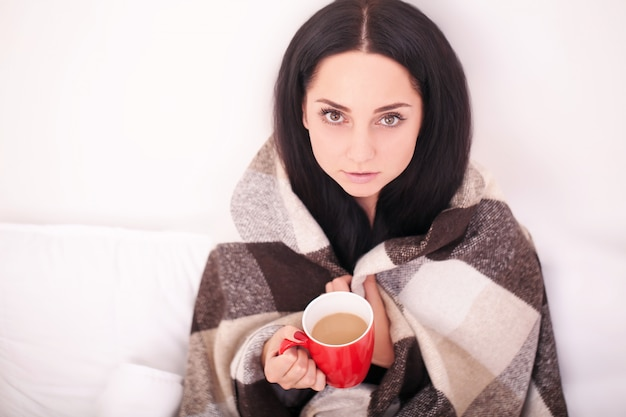 Jovem doente com febre, bebendo uma xícara de chá quente