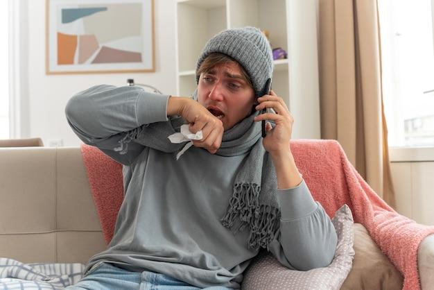 Jovem doente com lenço no pescoço, chapéu de inverno, segurando a mão perto da boca e falando ao telefone, sentado no sofá da sala