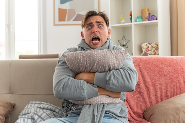 Jovem doente com medo com um lenço no pescoço abraçando o travesseiro sentado no sofá da sala de estar