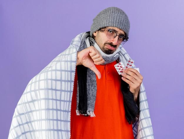Jovem doente com óculos, chapéu de inverno e cachecol embrulhado em xadrez segurando pacotes de cápsulas olhando para a frente, mostrando o polegar para baixo isolado na parede roxa