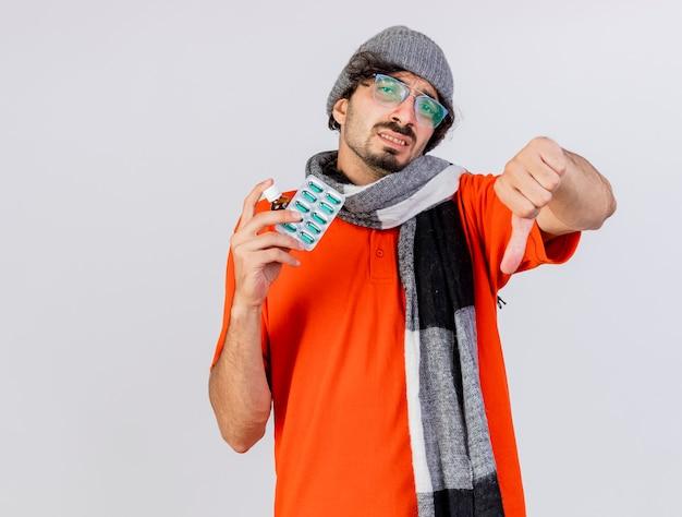 Jovem doente com óculos, chapéu e lenço de inverno mostrando medicamento em vidro e pacote de cápsulas e polegar para baixo, olhando para frente, isolado na parede branca