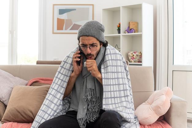 Jovem doente com óculos ópticos embrulhado em xadrez com lenço no pescoço e chapéu de inverno tossindo falando no telefone sentado no sofá da sala