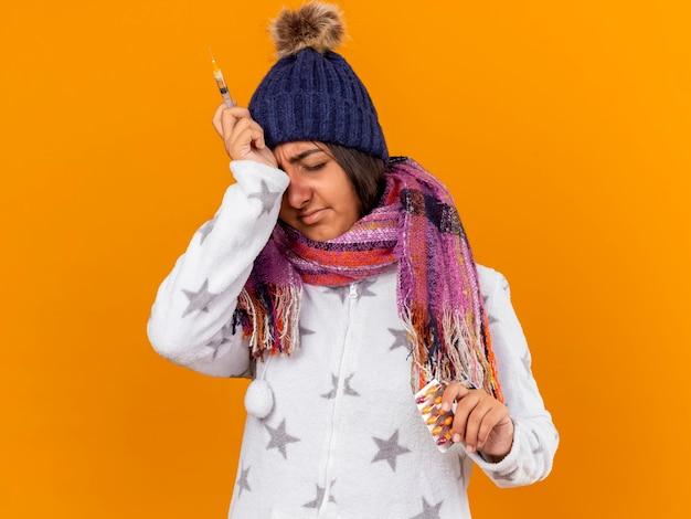Jovem doente com olhos fechados, usando chapéu de inverno com lenço segurando comprimidos com seringa e colocando a mão na testa isolada em fundo amarelo
