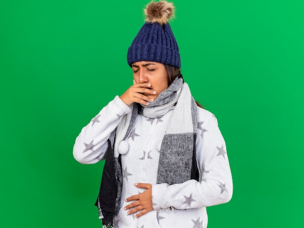 Jovem doente com tosse com chapéu de inverno e lenço colocando a mão na barriga isolada sobre fundo verde