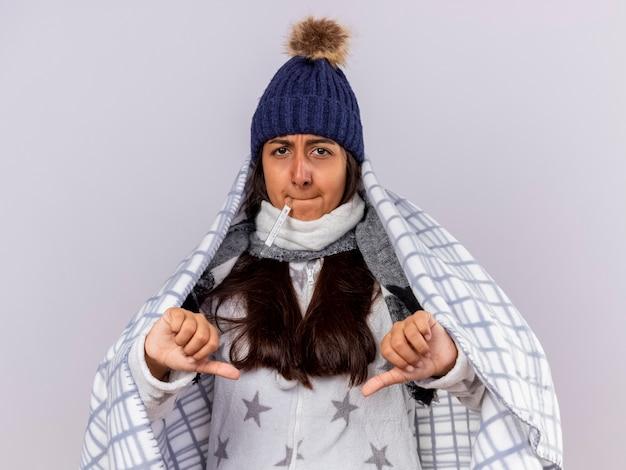 Jovem doente com um chapéu de inverno e um lenço embrulhado em xadrez colocando o termômetro na boca