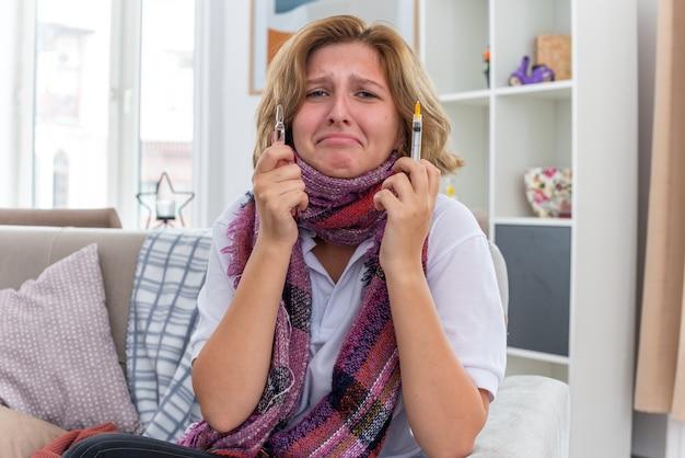 Jovem doente com um lenço quente em volta do pescoço, sentindo-se mal e doente, sofrendo de resfriado e gripe, segurando uma seringa e uma ampola, parecendo preocupada e assustada, sentada no sofá em uma sala iluminada