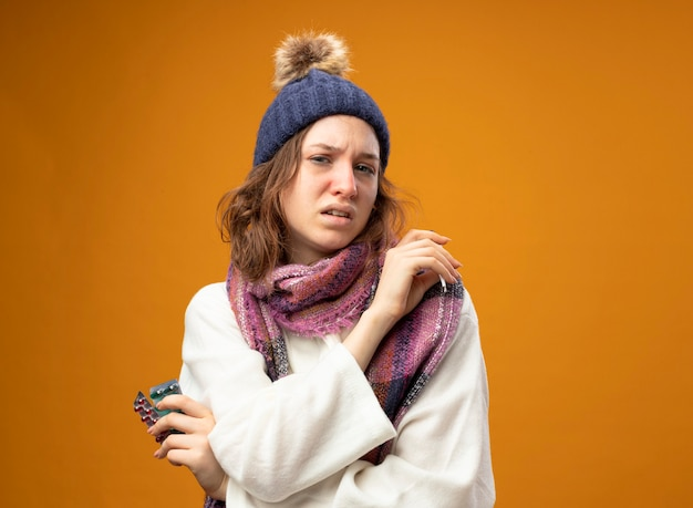 Jovem doente com um manto branco e chapéu de inverno com lenço segurando o termômetro com comprimidos e cruzando as mãos isoladas em laranja
