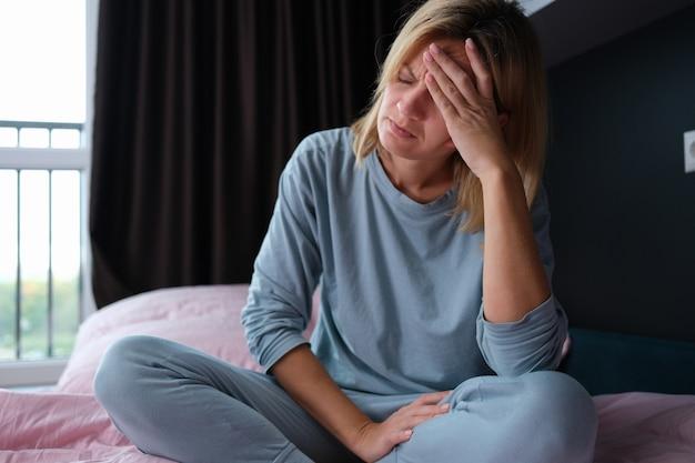 Jovem doente de pijama, sentada na cama e segurando a cabeça