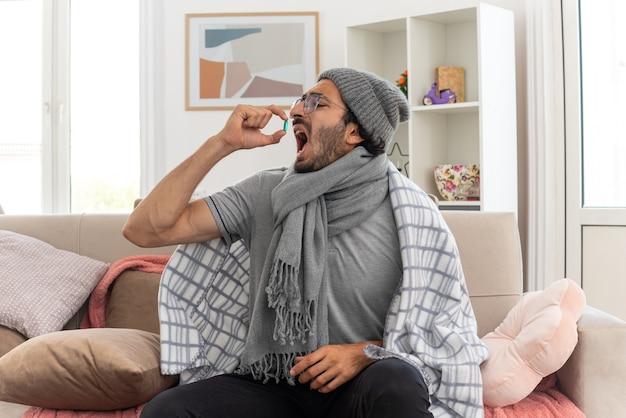 Jovem doente, desagradável, com óculos ópticos embrulhado em manta e lenço em volta do pescoço, chapéu de inverno, tomando pílula médica, sentado no sofá da sala