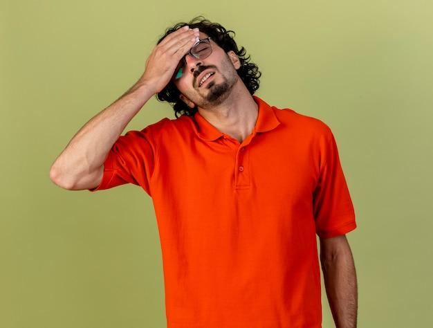 Jovem doente e dolorido, usando óculos segurando um guardanapo, tocando a testa com os olhos fechados, isolado na parede verde oliva