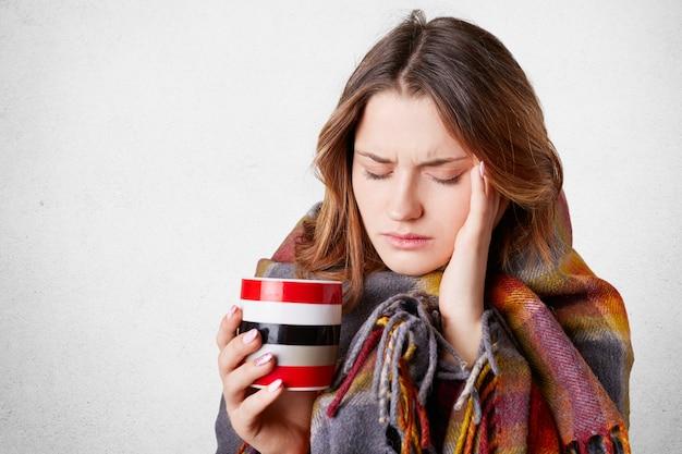 Jovem doente e frustrada, coberta por um cobertor quente, mantém a mão no templo, sofre de uma terrível dor de cabeça, bebe bebida quente, tenta se aquecer