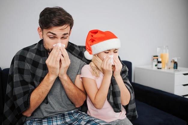 Jovem doente e pequena menina espirros em guardanapo branco. eles pegaram um resfriado. garota usar chapéu de natal. família sente-se em um quarto na cama.
