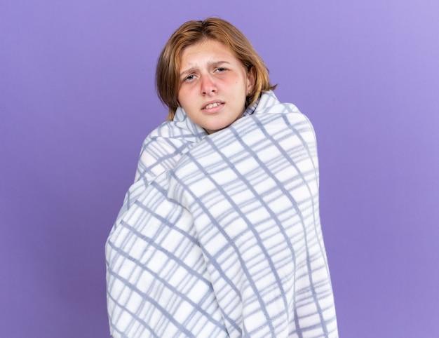 Jovem doente enrolada em um cobertor quente sentindo-se doente, sofrendo de um vírus