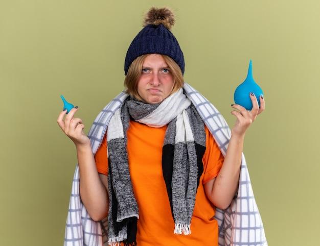 Jovem doente enrolada em um cobertor, usando chapéu e lenço, sentindo-se indisposta segurando enemas, parecendo confusa e descontente