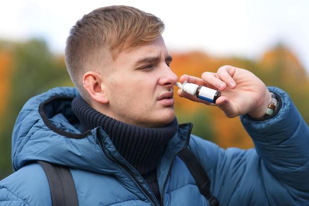 Jovem doente goteja injetando gota nasal para nariz entupido em um cara bonito com corrimento nasal