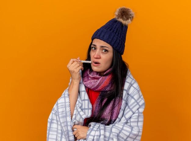 Jovem doente impressionada com chapéu de inverno e lenço embrulhado em xadrez colocando o termômetro na boca, olhando para a frente, isolado na parede laranja