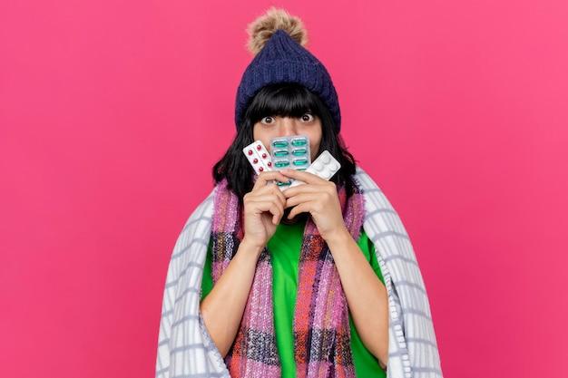Jovem doente impressionada com chapéu de inverno e lenço embrulhado em xadrez segurando pacotes de comprimidos médicos na frente da boca, olhando para a frente, isolado na parede rosa com espaço de cópia