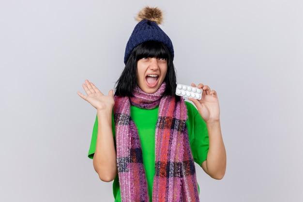 Jovem doente impressionada com chapéu e lenço de inverno mostrando pacote de comprimidos e a mão vazia olhando para cima isolado na parede branca