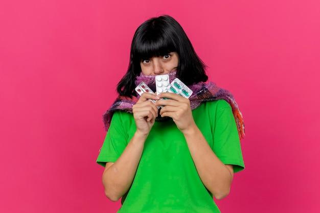 Jovem doente impressionada com lenço segurando comprimidos médicos, olhando para a frente, isolada na parede rosa com espaço de cópia
