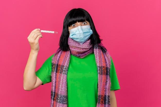 Jovem doente impressionada com máscara e lenço segurando o termômetro horizontalmente, olhando para a frente, isolada na parede rosa com espaço de cópia