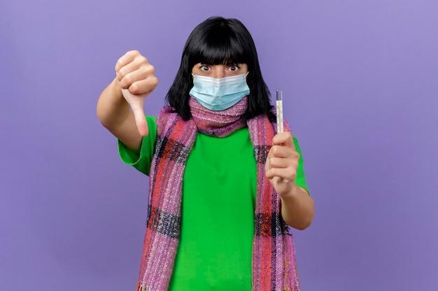 Jovem doente impressionada com máscara e lenço segurando o termômetro, olhando para a frente, mostrando o polegar para baixo isolado na parede roxa com espaço de cópia