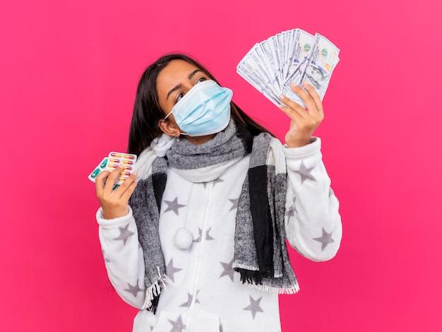 Jovem doente impressionada com máscara médica com lenço segurando comprimidos e olhando para dinheiro na mão isolada em rosa