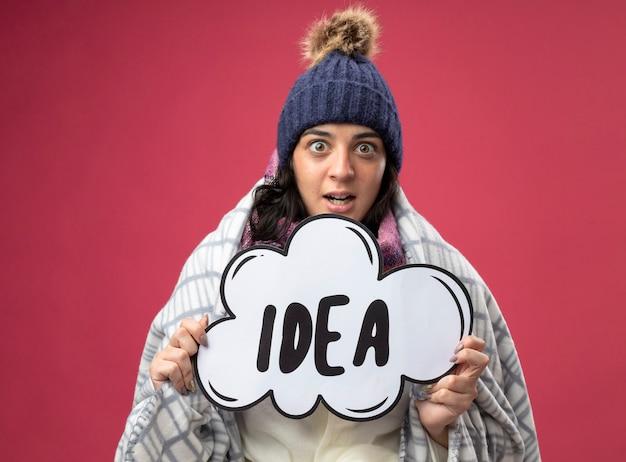 Jovem doente impressionada com um manto de inverno, chapéu e lenço embrulhado em xadrez segurando uma bolha de ideias, olhando para a frente, isolada na parede rosa