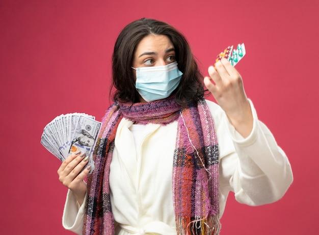 Jovem doente impressionada usando manto e lenço com máscara segurando dinheiro e pacotes de cápsulas médicas olhando para as cápsulas isoladas na parede rosa